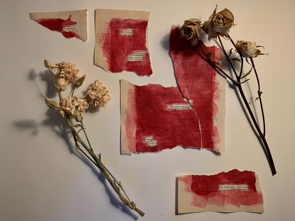 daughter growing innocent, take control, build your happiness crying softly the earth sighs and I rise. (This erasure poem is on a sheet of stained paper which has been torn into five large pieces, and arranged and photographed on a table alongside two dying flowers)